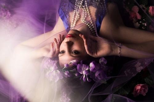 woman-with-purple-flower-headress-holding-cheeks-2524954